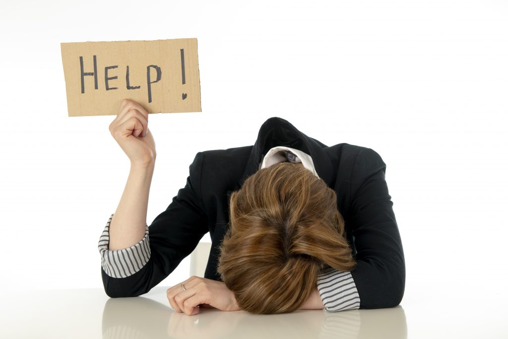 overwhelmed female head down holding up a help sign